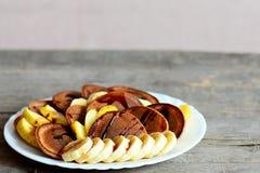 Panquecas do chocolate com bananas, maçãs e molho do caramelo em uma placa branca isolada no fundo de madeira com espaço da cópia Foto de Stock