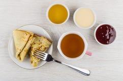 Panquecas dobradas, doce, mel, leite condensado, forquilha, copo do chá foto de stock