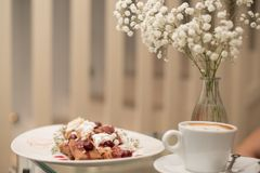 Panquecas e café decorados com as flores no vaso Imagens de Stock