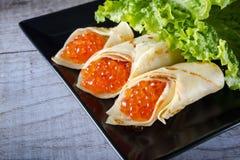 Panquecas enchidas pelo caviar dos salmões vermelhos horizontal imagens de stock