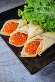 Panquecas enchidas pelo vertical do caviar dos salmões vermelhos fotografia de stock