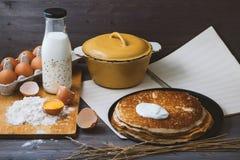 Panquecas frescas, quentes em uma frigideira, ovos, leite, farinha em uma tabela de madeira Imagem de Stock