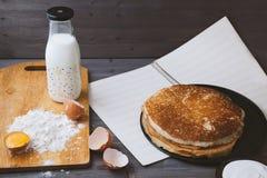 Panquecas frescas, quentes em uma frigideira, ovos, leite, farinha em uma tabela de madeira Imagens de Stock