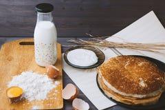 Panquecas frescas, quentes em uma frigideira, ovos, leite, farinha em uma tabela de madeira Fotos de Stock