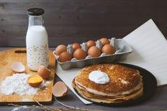 Panquecas frescas, quentes em uma frigideira, ovos, leite, farinha em uma tabela de madeira Imagem de Stock Royalty Free