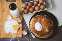 Panquecas frescas, quentes em uma frigideira, ovos, leite, farinha em uma tabela de madeira Vista superior Imagens de Stock