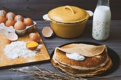 Panquecas frescas, quentes em uma frigideira, ovos, leite, farinha em uma tabela de madeira Vista superior Imagem de Stock Royalty Free