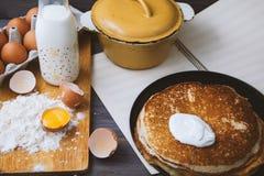 Panquecas frescas, quentes em uma frigideira, ovos, leite, farinha em uma tabela de madeira Vista superior Fotos de Stock Royalty Free