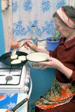Panquecas idosas de uma fritada da mulher Fotos de Stock Royalty Free