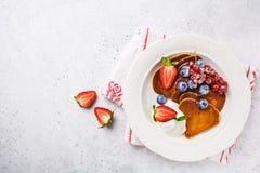 Panquecas na forma do coração com bagas, frutos e creme em uma placa branca, vista superior do coalho Conceito do dia do ` s do V imagens de stock