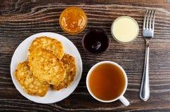 Panquecas na placa, bacias do requeijão com doce alaranjado, leite condensado, doce de cereja, copo do chá, forquilha na tabela V imagem de stock