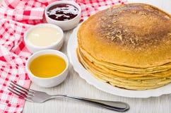 Panquecas no prato, doce de morango, mel, leite condensado, forquilha, n fotografia de stock