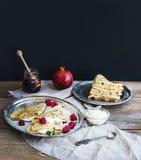 Panquecas ou crepes finos com framboesa fresca, creme, hortelã, em uma mesa de madeira rústica Fotos de Stock Royalty Free