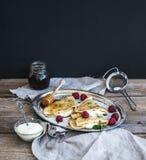 Panquecas ou crepes finos com framboesa fresca, creme, hortelã, na Foto de Stock