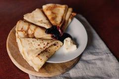 Panquecas para o café da manhã com leite em uma toalha Panquecas saborosos com xarope e manteiga do mirtilo Imagem de Stock