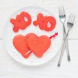 Panquecas vermelhas de veludo com sinal, abraços e beijos, e coração na placa branca, vista superior do xo, formato quadrado Foto de Stock