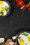 Pans with fried eggs. Tomatoes and bread on old metal background, top view. Food. Breakfast. Healthy food stock photos