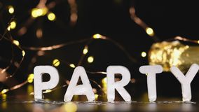 Pans shot of party word on black table with light bokeh and bottle of champagne,Celebration holiday event stock video footage