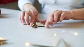 Panschot van vrouwenhanden die origamidocument ster voor Kerstmisdecoratie vouwen stock videobeelden