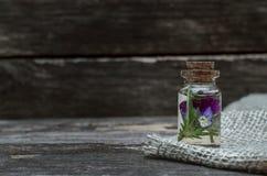 Pansies flower essential oil. Herbal medicine. Naturopathy. Pansy flower essential oil on wooden background. Herbal medicine. Naturopathy royalty free stock photo