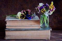 Pansies und alte Bücher stockfoto