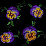 Pansy embroidery flower patch. Stitch texture effect. Traditional floral fashion decorationseamless pattern. Purple violet yellow Royalty Free Stock Image