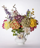 Pansy Vase Filled with Silk Hydrangea, Rose, and Cornflowers. Image is of a white ceramic vase with hand-painted pansies on it filled with colorful silk flowers stock photography