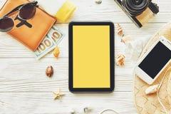 Pantalla amarilla vacía de la tableta con el espacio para el texto viaje pl del verano Imagenes de archivo