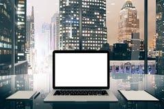 Pantalla blanca en blanco del ordenador portátil en la tabla vidriosa en oficina moderna con Foto de archivo libre de regalías