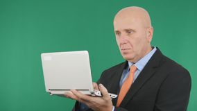 Pantalla confiada del verde de Working With Laptop del hombre de negocios en fondo foto de archivo