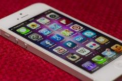Pantalla de IPhone 5 Apps en una superficie roja Foto de archivo libre de regalías