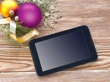 Pantalla de la tableta de la PC en la madera con la decoración de Navidad Foto de archivo libre de regalías