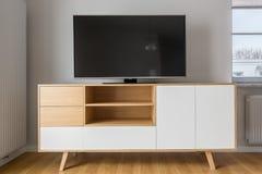 Pantalla de la televisión en el gabinete de madera imagen de archivo