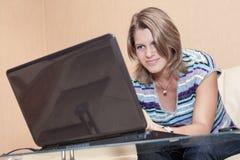 Pantalla de observación de la mujer caucásica joven con sonrisa, usando el ordenador portátil en casa Imágenes de archivo libres de regalías