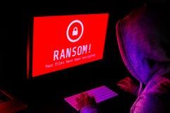 Pantalla de ordenador con alarmas del ataque del ransomware en rojo y un hacke fotos de archivo libres de regalías