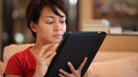 pantalla de tableta conmovedora de la muchacha en casa almacen de video