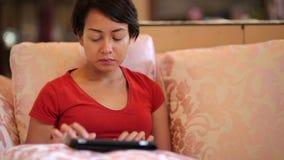 pantalla de tableta conmovedora de la muchacha en casa almacen de metraje de vídeo