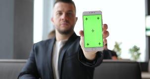 Pantalla del verde de la demostración del hombre de negocios del smartphone, indicador digital vacío almacen de video