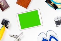 Pantalla en blanco de la tableta rodeada por los accesorios del viaje Imagenes de archivo