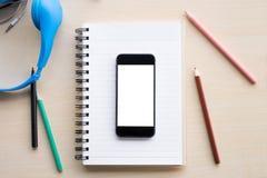pantalla en blanco de la visión superior del teléfono móvil en el cuaderno y el DES de madera Imagenes de archivo