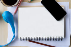 pantalla en blanco de la visión superior del teléfono móvil en el cuaderno y el DES de madera Fotografía de archivo libre de regalías