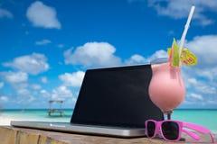 Pantalla en blanco del ordenador portátil en el escritorio de madera con la playa Relaje el concepto fotos de archivo