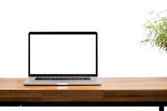 Pantalla en blanco del ordenador portátil en la tabla de madera Imágenes de archivo libres de regalías