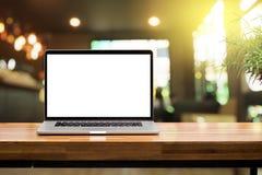 Pantalla en blanco del ordenador portátil en la tabla de madera Imagen de archivo libre de regalías