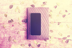Pantalla en blanco del smartphone con el diario en la tabla de madera con el leav Imagenes de archivo