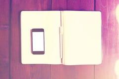 Pantalla en blanco del smartphone con las páginas en blanco del diario en la tabla de madera, Fotos de archivo libres de regalías