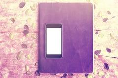Pantalla en blanco del smartphone con un libro de ejercicio en la tabla de madera Foto de archivo