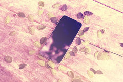 Pantalla en blanco del teléfono celular en la tabla de madera con las hojas Imagen de archivo libre de regalías