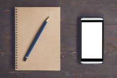 Pantalla en blanco en blanco del cuaderno y del teléfono para hacer publicidad en la madera TA Foto de archivo libre de regalías