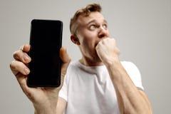 Pantalla hermosa joven del smartphone de la demostración del hombre aislada en fondo gris en choque con una cara de la sorpresa imagen de archivo